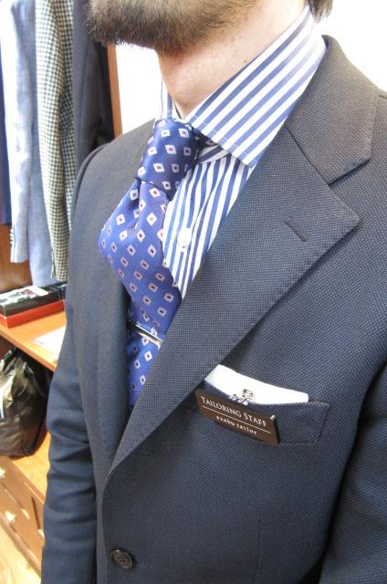 無地のネイビースーツにブルーの太ストライプシャツ、ブルー小紋タイを合わせたクラシックスタイル。