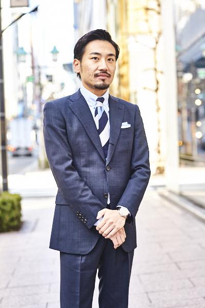 王道であるネイビーのグレンチェックスーツに、タブカラーのシャツを合わせることで程よく個性を出しました。 – Azabu Tailor Style